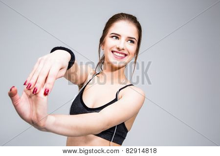 Portrait of a smiling sports woman stretching hands over gray background
