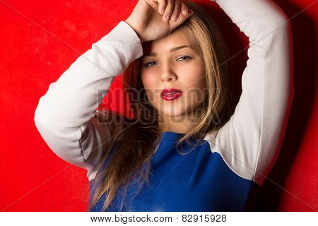 Portrait Of Sexy Blonde Woman In Hoodie Leaning Against Red Wall