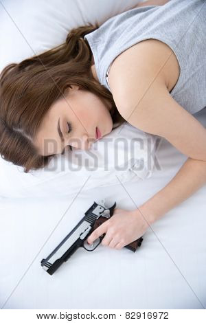 Woman in bed sleeps with hand on gun weapon home security