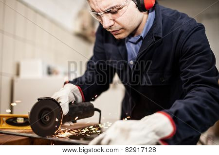 Worker using a grinding machine on a metal plate