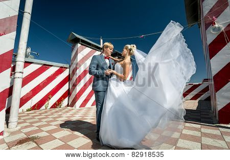 Newly Married Couple Posing On Skyscraper Roof Top At Windy Day