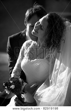 Black And White Romantic Portrait Of Groom Kissing Bride In Cheek