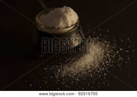 salt in the straw with a spoon. black background