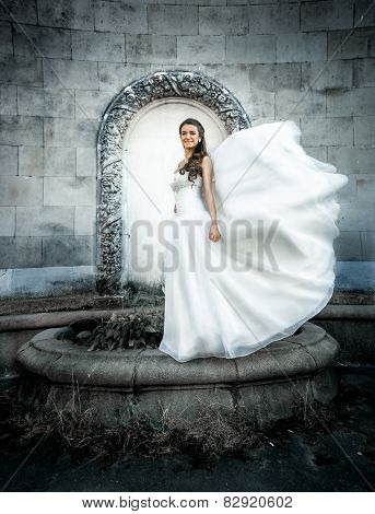Young Bride Posing At Old Castle While Wind Blows Her Veil