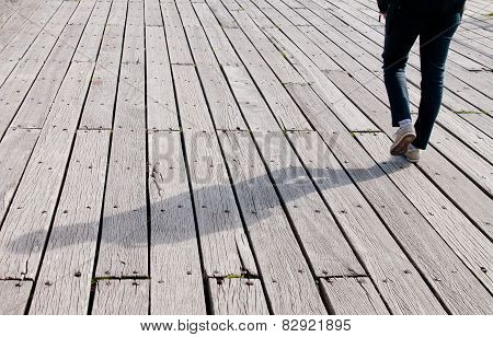 Young Adult Walking On A Wooden Footpath