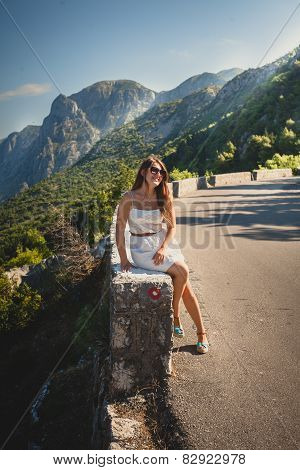 Young Woman Sitting On Side Of The High Mountain Road At Sunny Day