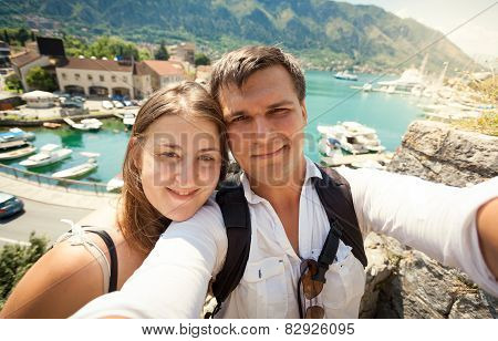 Young Happy Couple Posing Against Sea Bay At Sunny Day