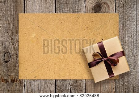 Gift Box And Vintage Paper On Old Wooden Background