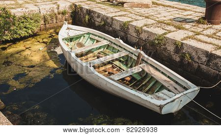 Wooden Rowboat Mooring To Ancient Stone Berth