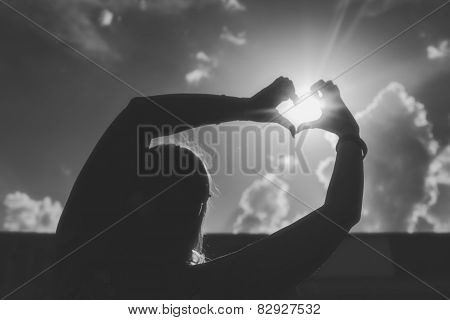 Silhouette of a girl shows a summer heart