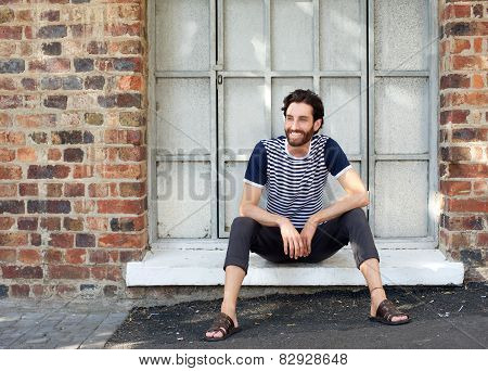 Happy Young Man With Striped Shirt Sitting On Windowsill