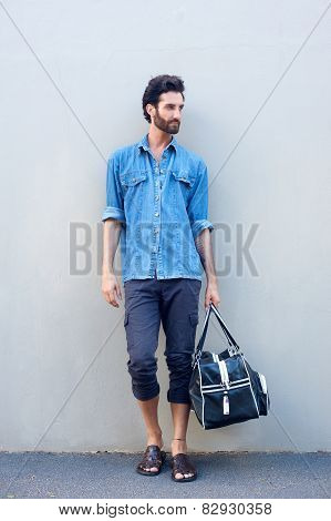 Male Fashion Model With Beard Holding A Travel Bag