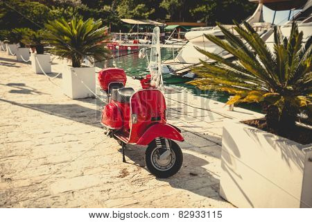 Toned Photo Of Retro Red Scooter Parked At Port