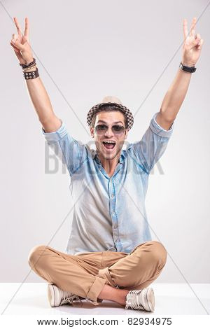 Happy young casual man celebration a victory. He is sitting with his legs crossed while holding both hands up, showing the victory gesture.