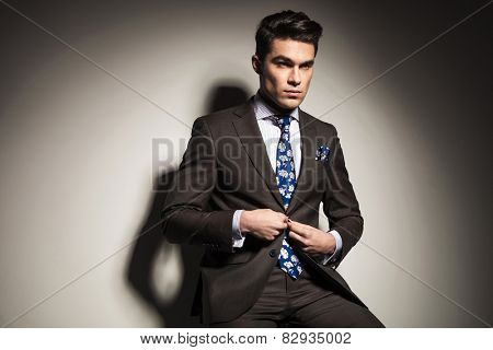 Handsome business man looking away from the camera while closing his button.