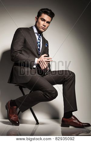 Side view picture of a young elegant business man sitting with one leg in front of the other, looking at the camera.