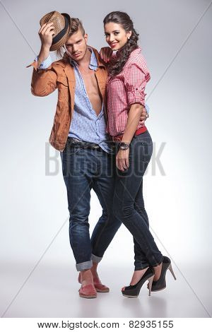 Handsome casual man taking off his hat while his girlfriend is smiling and leaning on him.