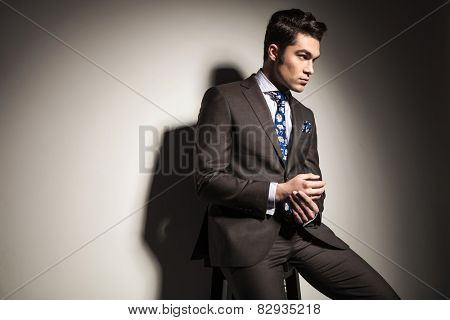 Side view picture of a elegant business man looking away from the camera while sitting on a stool.