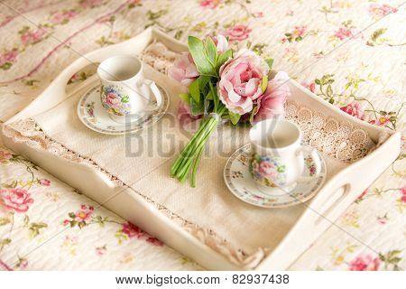 Vintage Tray With Flowers And Teacups Lying On Bed