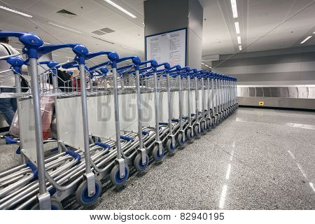 Ow Of Luggage Trolleys At Airport Terminal