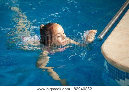 Girl Swimming To The Edge Of Swimming Pool