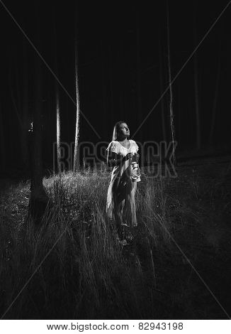 Monochrome Photo Of Woman In White Dress Walking At Forest At Night With Lamp