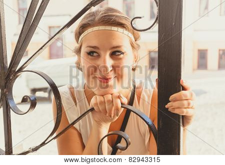Portrait Of Smiling Girl Leaning At Forged Gates