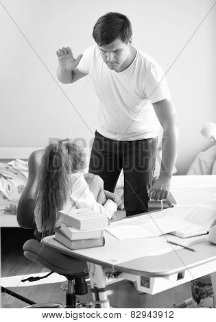 Monochrome Shot Of Angry Father Hitting Intimidated Daughter