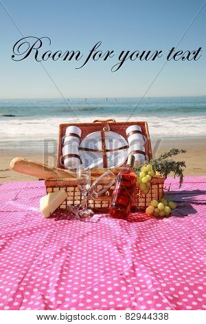 A beautiful Picnic in Laguna Beach in Southern California. Picnic Basket with French Bread, Wine, Grapes, Cheese, Flowering Rosemary Cuttings, and the Blue Paficic Ocean with Waves and Sand.