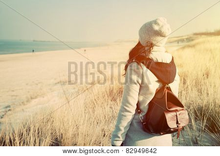Woman with retro backpack standing on the beach, dunes and looking at the sea. Vintage mood, adventure, travel