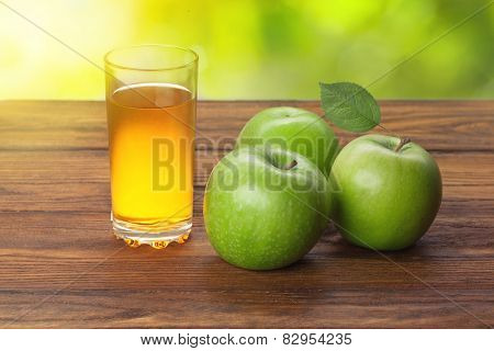 Glass of apple juice and apples on wooden background