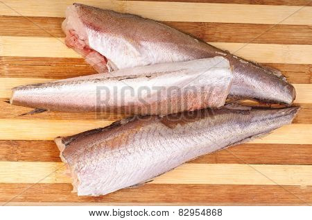 Frozen Fish Hake On Cutting Board Background