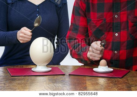 Woman And Man With Spoons Eating Hen And Ostrich Eggs