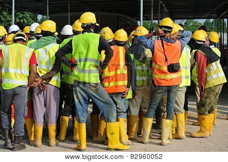 Group of construction workers assemble at the open space.