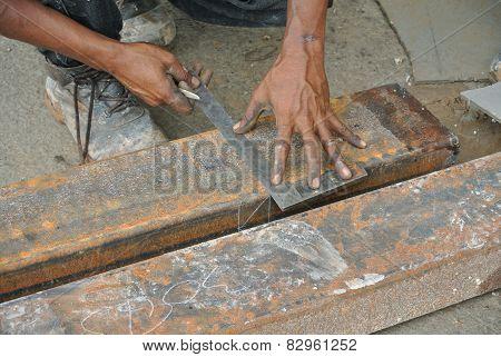 Workers using 90 degree steel ruler to measure mild steel