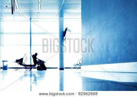 Passengers in contemporary hallway of airport waiting for departure