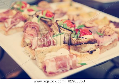 Various snacks in plate on banquet table, toned image
