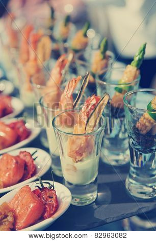 Glasses with seafood snacks -  banquet dish, toned image