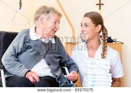 Nurse bringing supplies to senior woman in retirement home