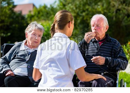 Seniors, couple of man and woman sitting in wheelchair, eating candy in garden of nursing home