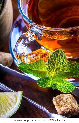Tea in a glass cup, mint leaves, dried tea, sliced lime, cane sugar
