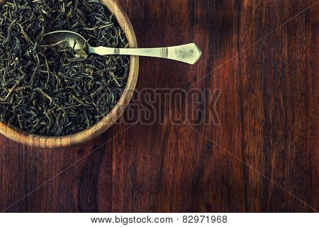 Dry tea in wooden plate, on wooden table. Antique spoon