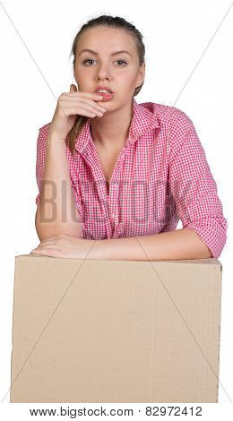 Sexy girl in shirt leaning on cardboard box, looking at camera