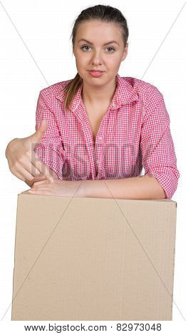 Sexy girl in shirt leaning on cardboard box and points finger at her