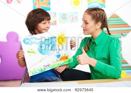 Teacher with thumb up looking at drawing of boy