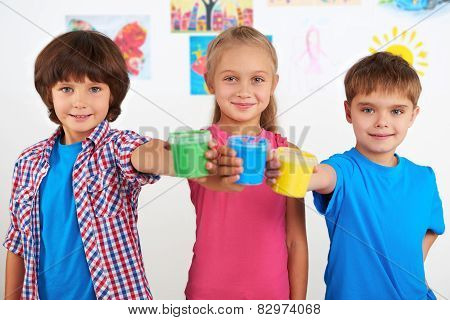 Children holding colorful cans with paint