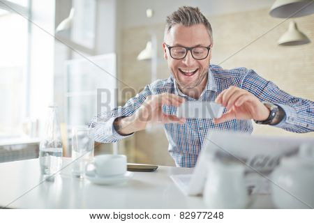 Businessman taking photo of newspaper article