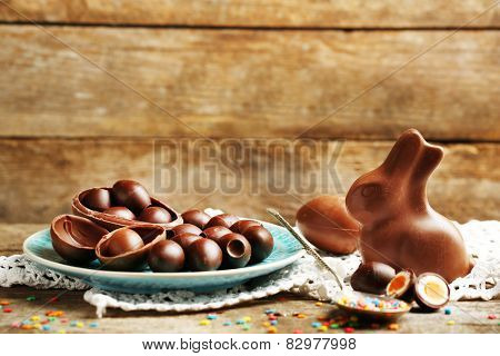 Chocolate Easter eggs and rabbit on plate, on wooden background