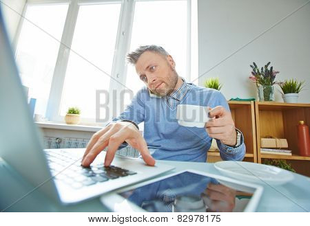 Businessman in casual working on latop, having tea and speaking on cellphone in office