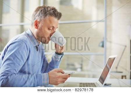Businessman in casualwear having tea while reading sms on cellphone in office